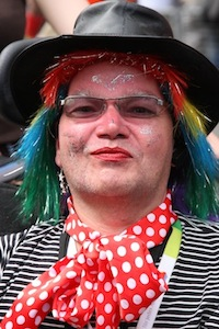 Photograph of a man in a dark hat and sunglasses, with a brightly coloured wig and make up on and a red and white spotted handkerchief around his neck, dressed for carnival or a parade.