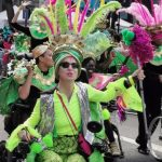 Colour photograph of wheelchair users dressed in bright green and pink clothes with feathered headdresses dancing in the street