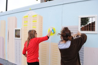 Colour photograph of two women painting a cityscape on a building site hoarding