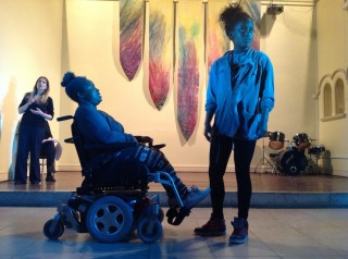 A young woman in a wheelchair is looking up at a young woman who is standing next to her but looking away.