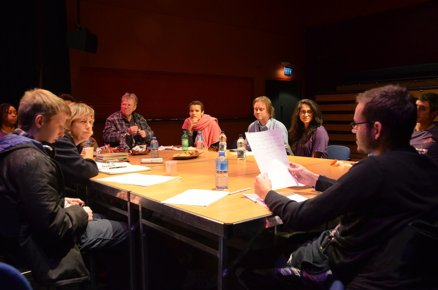 A group of people are sitting around a table in a studio theatre. In front of them are bottles of water and pieces of paper. One man is reading to the rest.