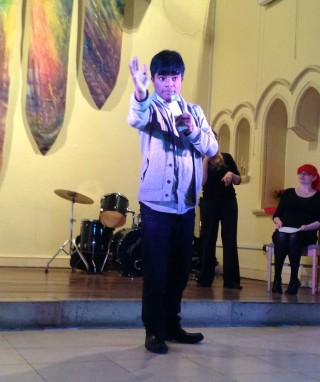 A young Asian man wearing a light-coloured jacket and dark trousers is raising his arm in gesture at the front of the stage.