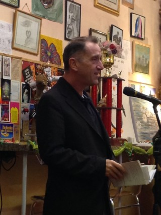 A middle-aged man with brown hair, wearing a dark jacket, is reading from a book. Behind him the wall is covered with paintings and notices.