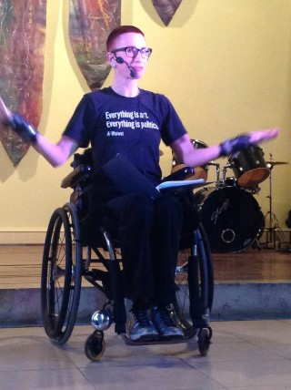 "A woman with short red hair and glass is signing as she sits in her wheelchair at the front of a stage. She is wearing a headset microphone, black trousers, silver boots and a T-shirt that reads: ""Everything is Art, Everything is Politics"" Ai Wei Wei. Sh"