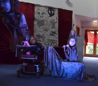 A small blonde woman operates a large puppet of an Inuit woman as she sits in her wheelchair. Behind her are two more Inuit puppet characters, and a wall hanging depicting Inuit myths,