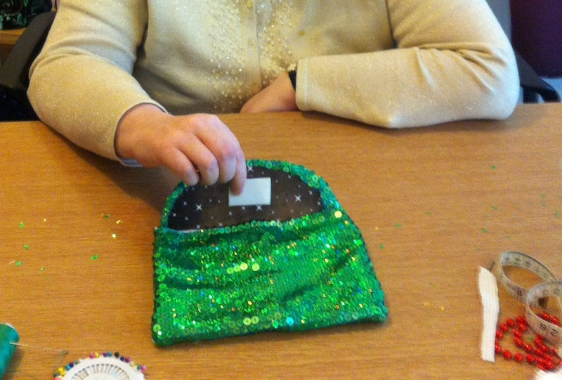 A green sequinned evening purse is being held out on top of a table by a woman wearing a yellow cardigan