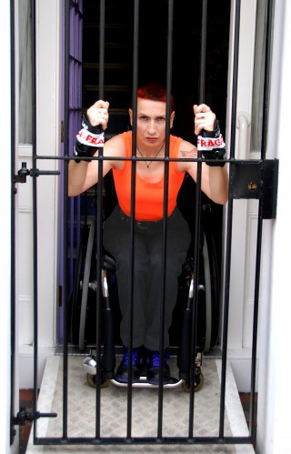A woman sits in her wheelchair, wearing black trousers and a bright orange vest. She has short hair and is scowling, tied to the security gate in front of her front door.