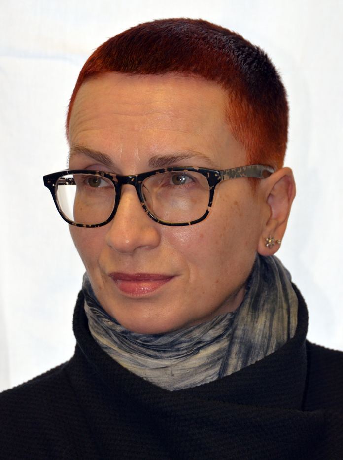 Head and shoulders shot of Ju Gosling AKA ju90, with short red hair and black glasses