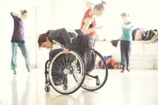 Photograph of woman dancing in a wheelchair with other dancers in the background.