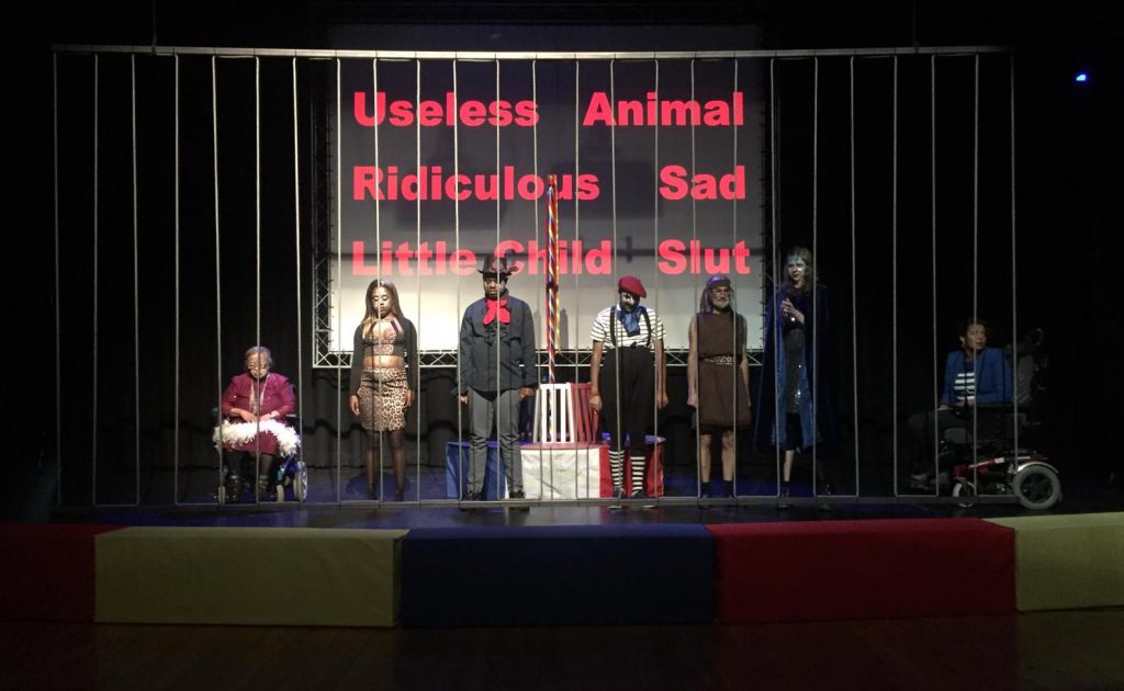 Colour photograph of a group of disabled people lined across the stage behind cage bars, with words including Useless, Animal and Sad projected behind them