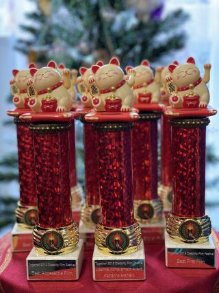 Colour photograph of red trophies with Feng Shui cats on top of each of them, waiting to be presented