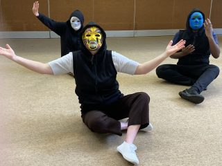 Colour photograph of three adults sitting on the floor, wearing black hoodies and hand-painted masks, making gestures with their arms