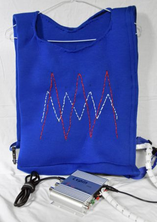 Photograph of a blue neoprene tabard on a hangar. The tabard is decorated with embroidery and a cable coming from it is connected to a mini-amplifier.