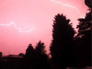 Colour photograph of lightning forking across a pink sky, with the outline of trees and houses in the foreground.