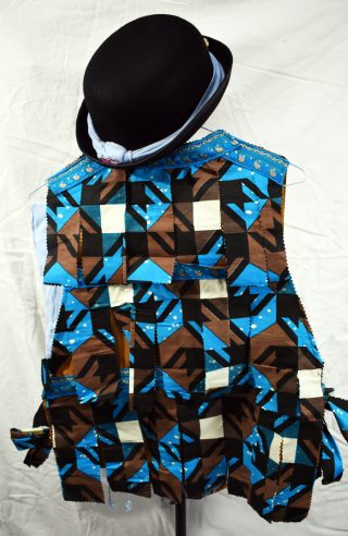 Back of the jacket, covered with blue and brown African fabric tatters and blue Indian trimming