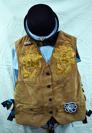 Sand-coloured suede-fronted jacket, with gold sequinned appliqué flowers on the breasts and various blue flower-themed badges