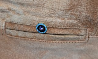 Close up of small blue enamelled flower badge on pocket