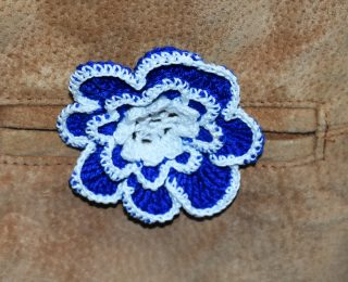 Close up of blue crocheted flower badge on pocket