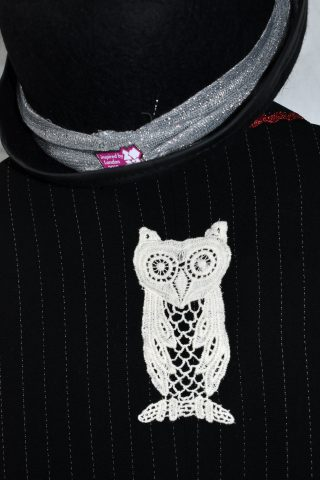 Close up of appliqué lace owl on the back of the jacket