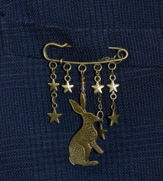 Close up of brass pin with hare and stars