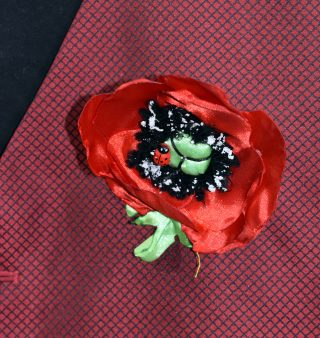Close up of fabric badge in the shape of a poppy