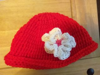 Red knitted cap incorporating a white crocheted flower
