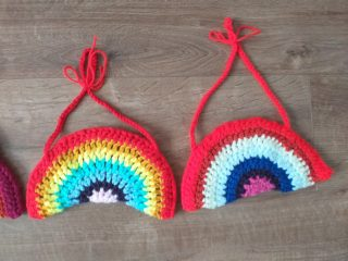 Pair of crocheted rainbows in brightly coloured wool.