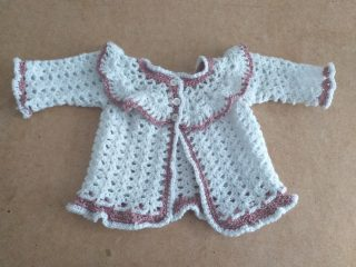 Knitted baby jacket in white with a pink trim