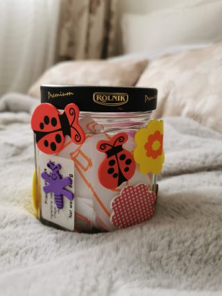 Plastic screw top jar with flower, ladybird and insect stickers on the outside and a drawing in orange pen on white paper inside.