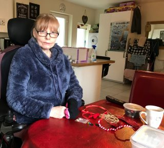Colour photograph of a woman sitting in a wheelchair working at her kitchen table, with craft materials and a cup of tea in front of her