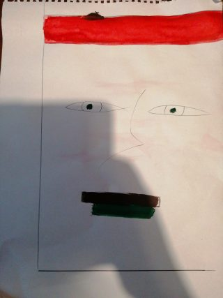 Pencil sketch of a stylised face looking out of a rectangle, with red paint added in a line at the top and black paint across the mouth. A shadow falls across the sketch of the man taking the photograph.