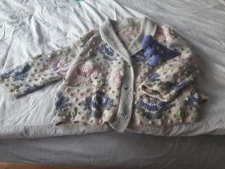 Photograph of an elaborately knitted baby's cardigan and a knitted toy, laying on a bed.