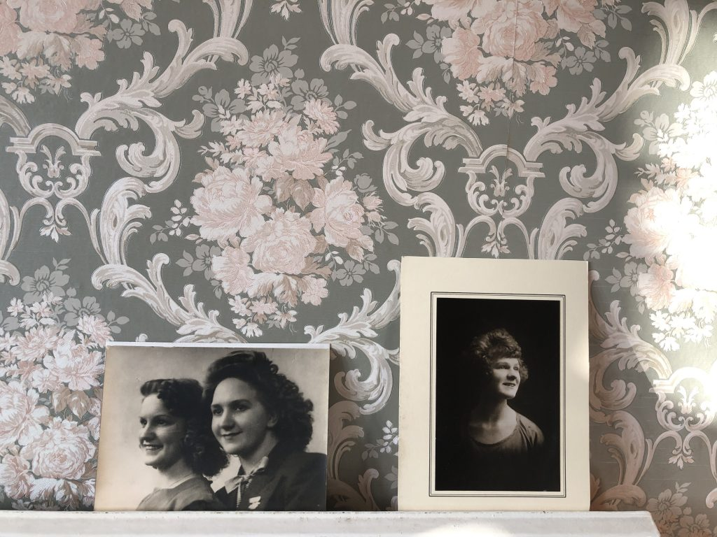 Two black and white portraits, one of one woman and one of two, are propped against grey and pale pink patterned wallpaper.
