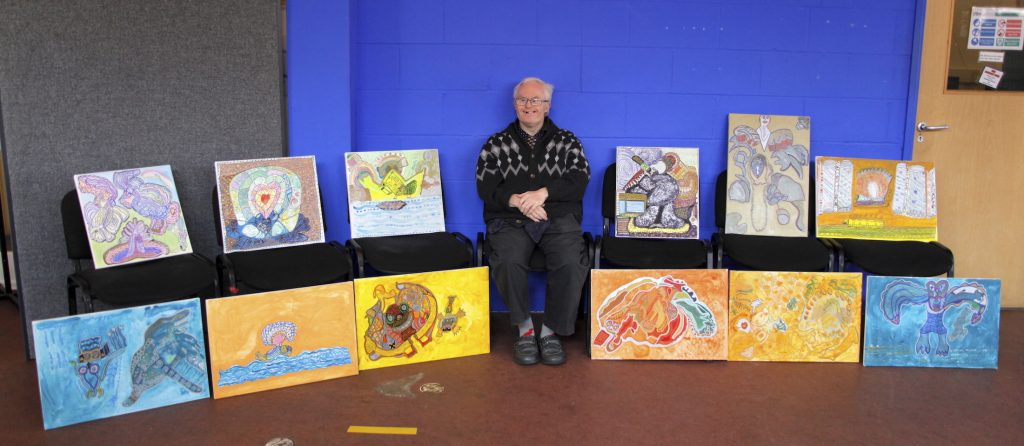 Photograph of man sitting down surrounded by canvases of his paintings