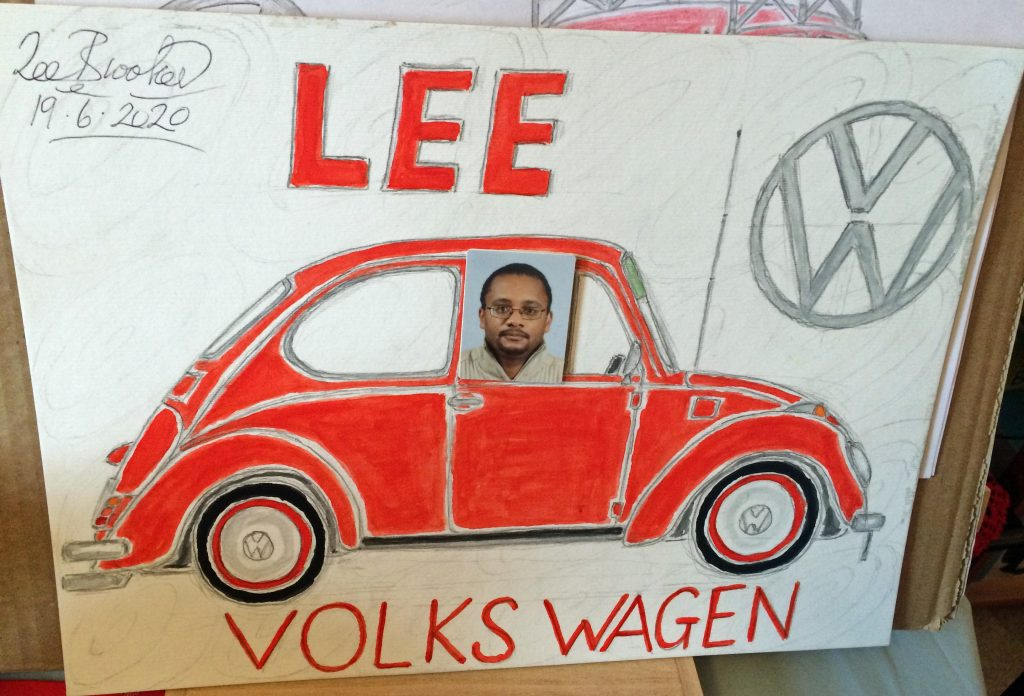 Painted sketch of a red VW Beetle car, with a photograph of the artist in the driver's window and the words Lee and Volkswagen in red paint.