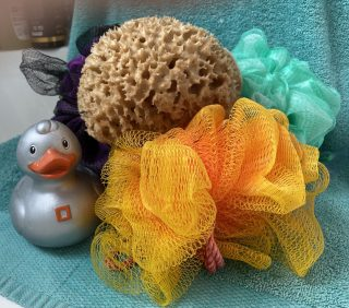 Orange, green and purple bath puffs sit on a turquoise hand towel, with a natural sponge on top, and a silver bath duck sitting on the left