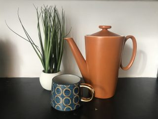 Photograph of a still life comprising of a brown coffee pot, a blue mug and a cream bowl of bulbs