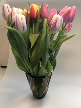 Yellow and pink tulips are displayed in a black shiny pot