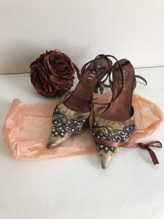 A pair of open-backed, high-heeled women's dance slippers are sitting on peach-coloured tissue paper. They have long leather ribbons to tie them on. Behind them is a corsage made of four bronze-coloured artificial roses, with a bronze ribbon trailing from them across the shoes.