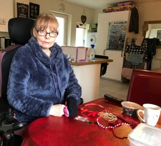 Tracy sits in her wheelchair at the table making crafts.