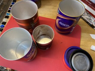 4 different empty kitchen cans with the lids off, each a different size.