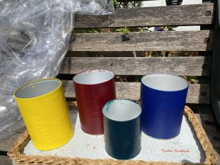 The painted cans drying outside.