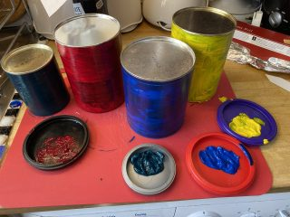 The tins are partway through being painted different colours, using their lids to hold the paint.