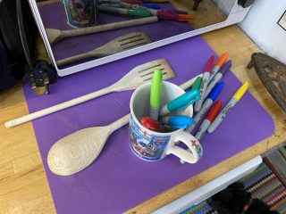 Photo of a wooden spoon and wooden spatula on a food mat with a mug full of felt-tipped pens