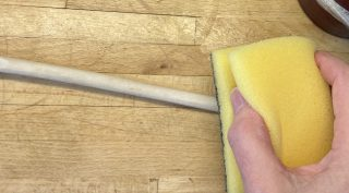 The scratchy side of the kitchen sponge is used to smooth down the wooden spoon.