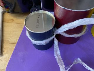 Cling film being tied around the painted cans.