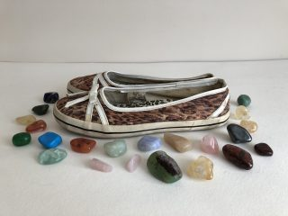 A pair of leopardskin printed canvas women's shoes with rubber soles are sitting on a white surface surrounded by polished semi-precious stones.