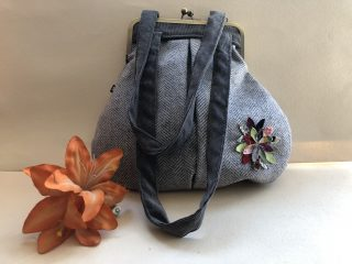Still life image: a grey purse-shaped handbag with grey ribbon-like carry handles has a multicoloured felt flower embroidered on it. In front and to the left is an artificial orange lily flower.