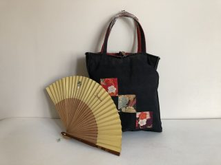 Still life with a black cotton bag resting on a white surface against a white wall with an open Japanese fan in front of it. The bag has three patches going down diagonally across the front with floral designs.